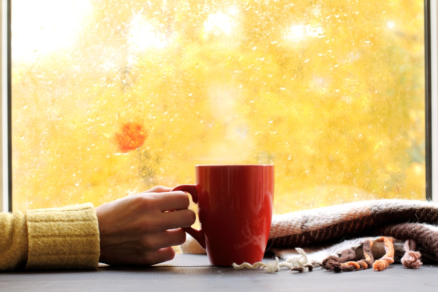 red mug of hot drink, when behind a window is rain in autumn in Beaverton, OR